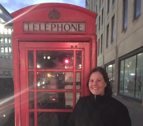 International Product Operations Manager Melanie Peterson standing in front of a telephone booth